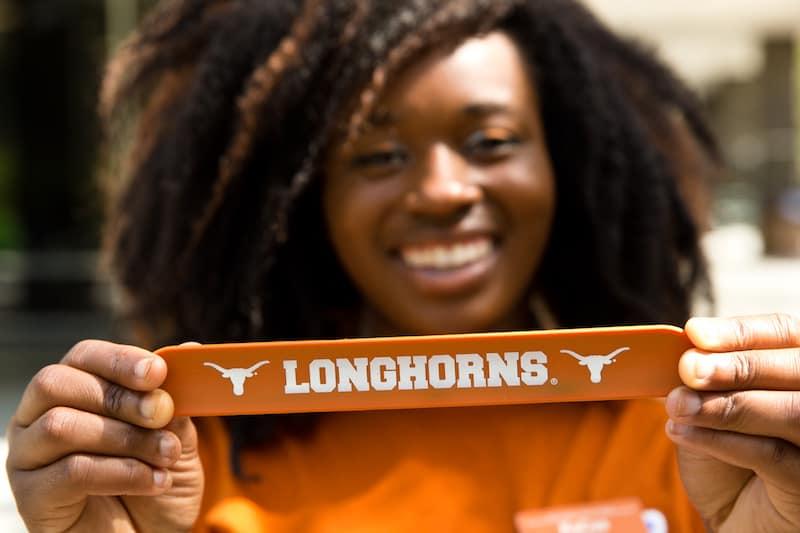student holding longhorn sign