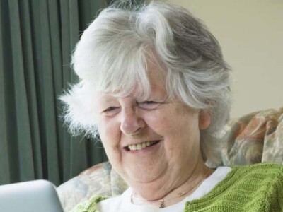 older woman holding a laptop